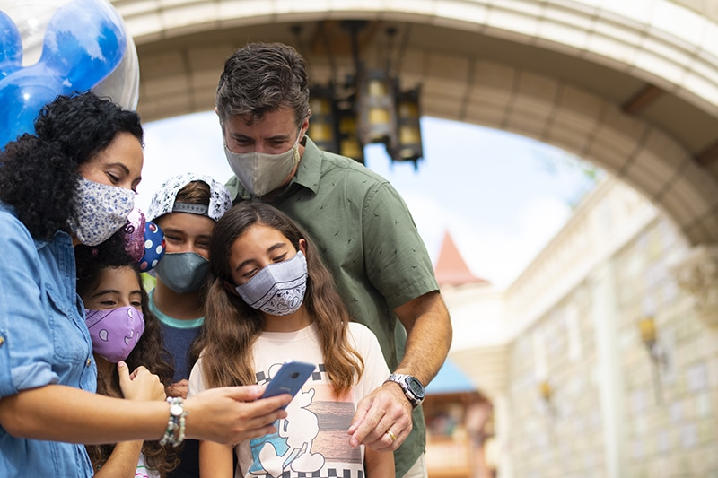 A family wearing masks at Walt Disney World Resort while looking at a smartphone.