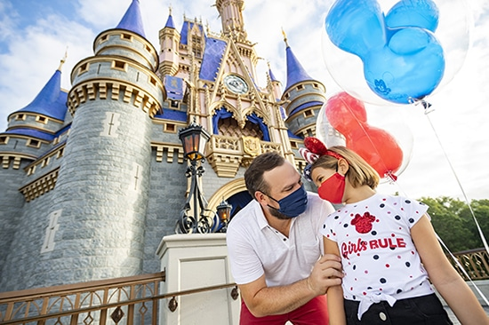 A father & daughter wearing masks in front of Cinderella Castle at Disney's Magic Kingdom Theme Park