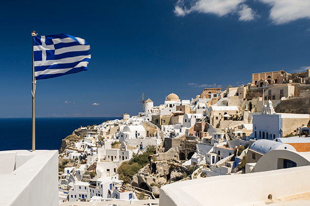 A flag of Greece waving above a beautiful city.