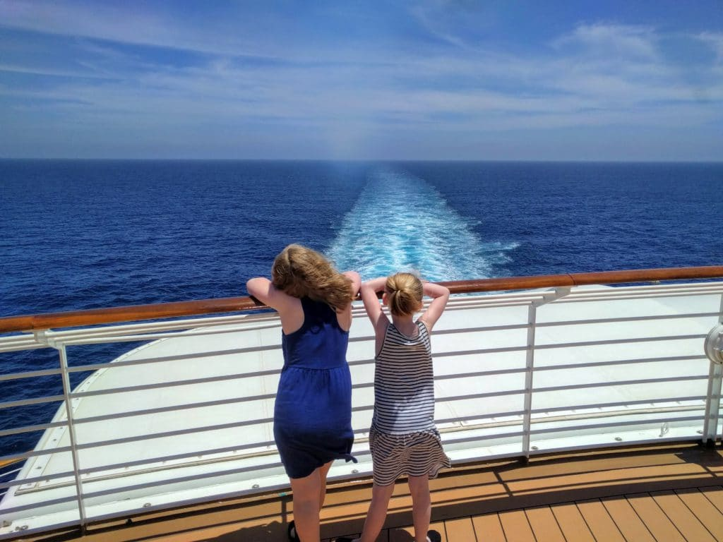 Two girls looking out to sea at the back of a Disney Cruise